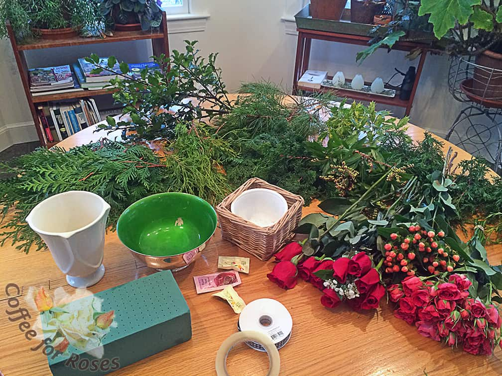 Pick your containers first. I used a silver-plated Revere bowl, a white garage sale vase, and a basket lined with a washed cottage cheese carton.  Next, pick assorted evergreens from your yard. I used Green Giant arborvitae, eastern red cedar (J. virginiana), hinoki false cypress, Gold Mop cypress, Pieris (aka andromeda), pitch pine, blue holly, and variegated Osmanthus.   Add flowers from the supermarket  - I picked roses and Hypericum berries.  You also need Oasis floral foam, waterproof tape, and ribbon if desired.