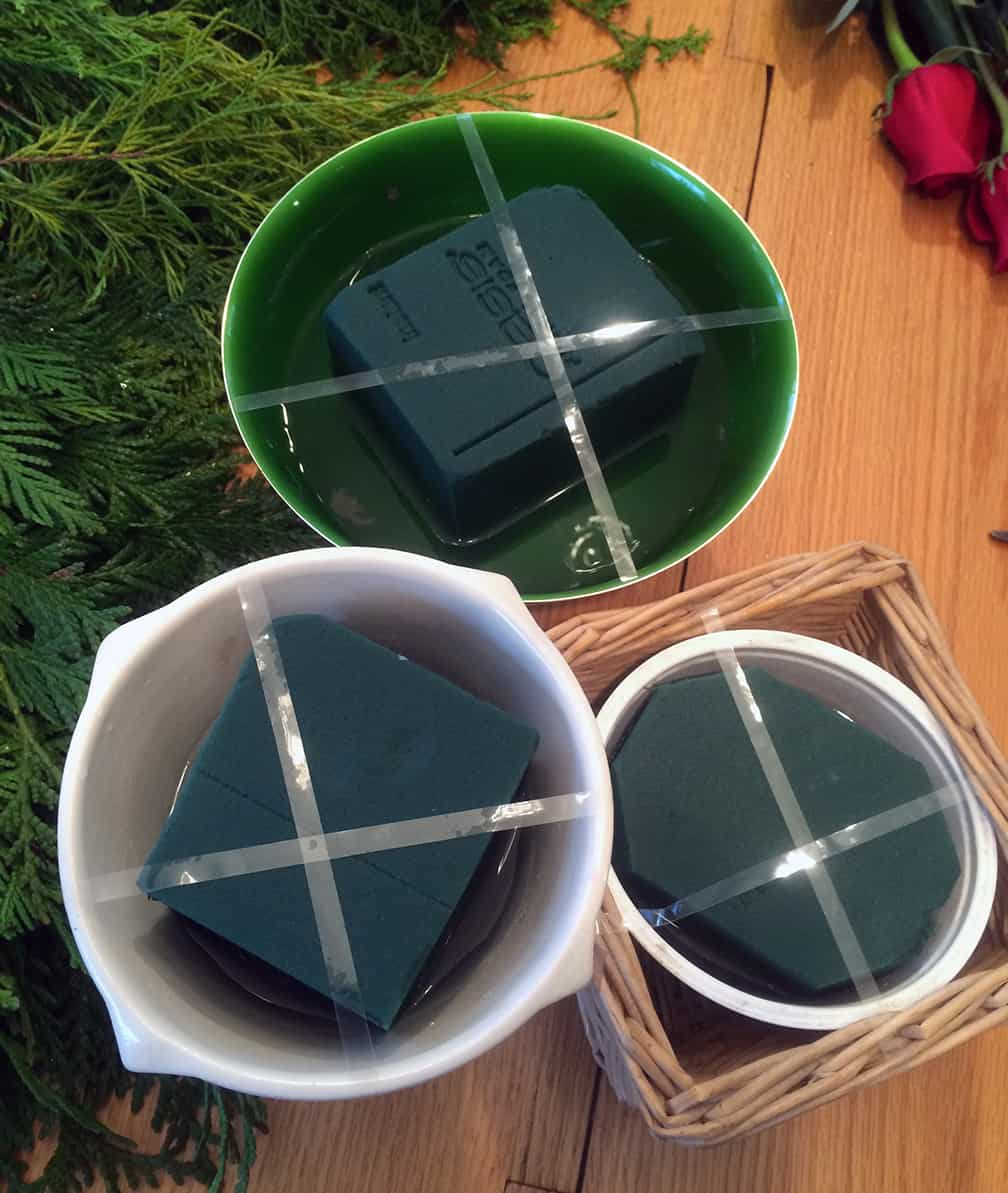 Put the soaked Oasis in the containers and use waterproof florist's tape to secure it in the containers.