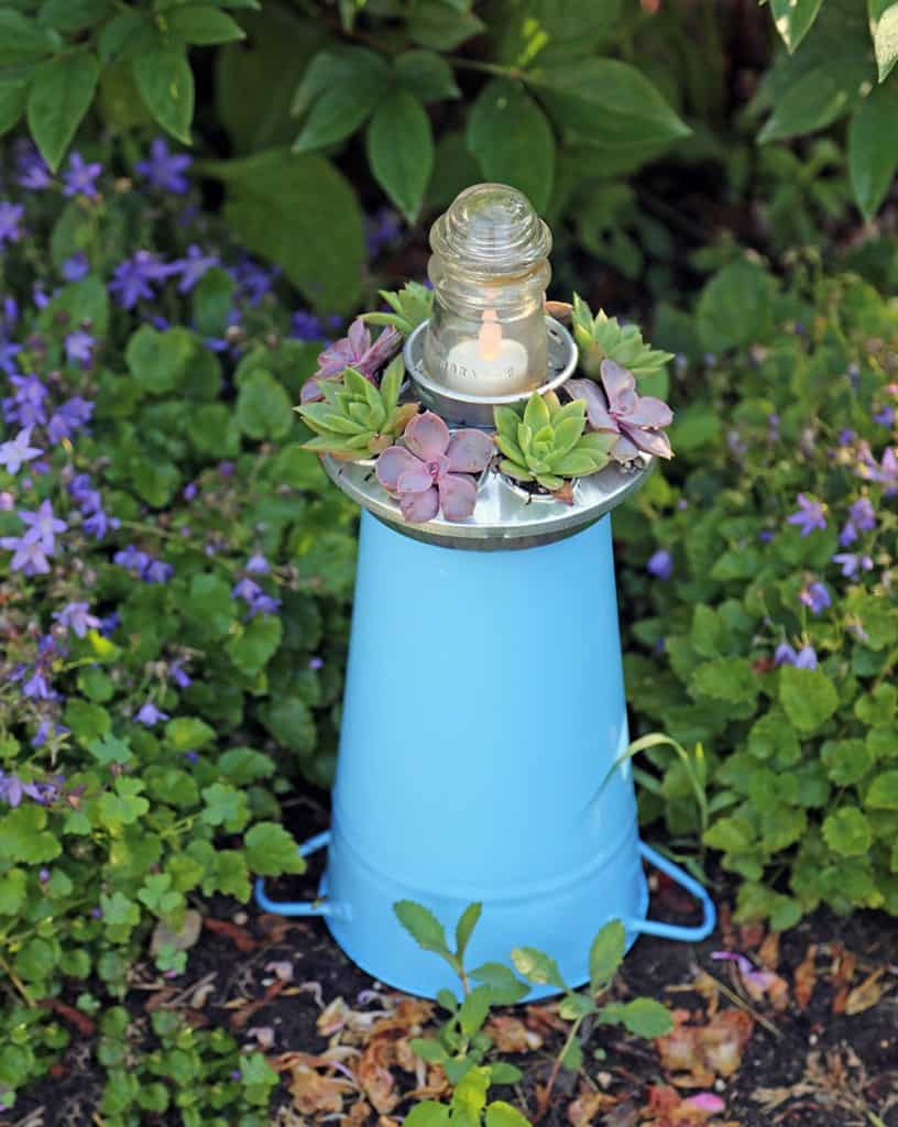 Here's a blue enamel bucket placed in the garden. You could combine a collection of several lighthouses together, or use several to line and light a path.