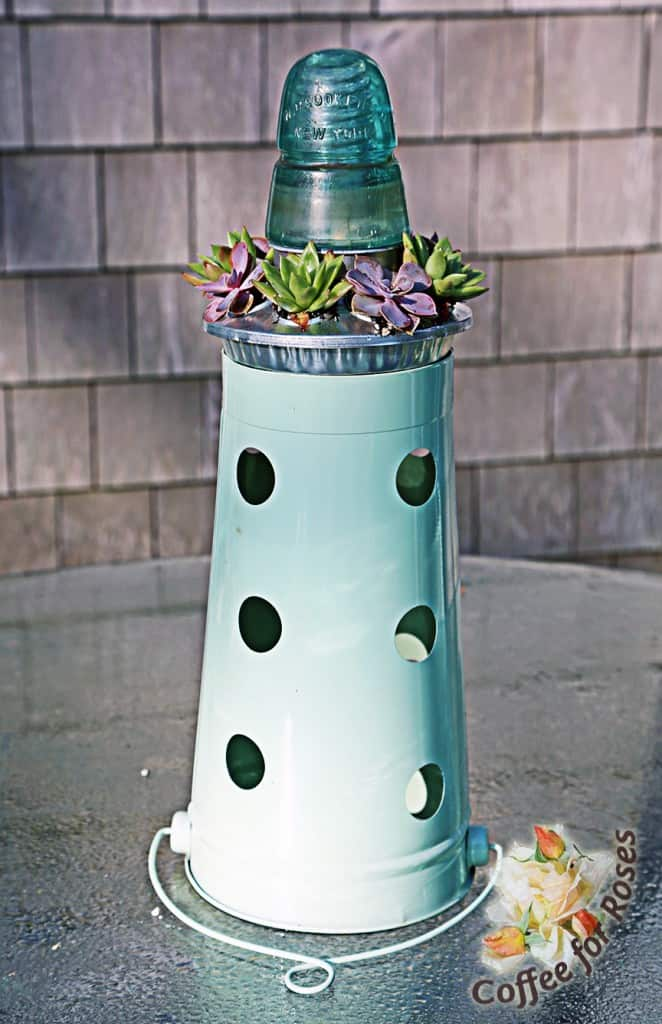 I found this green florist bucket at a crafts store. Why the holes? I have NO idea. But it worked well with this turquoise insulator on top.