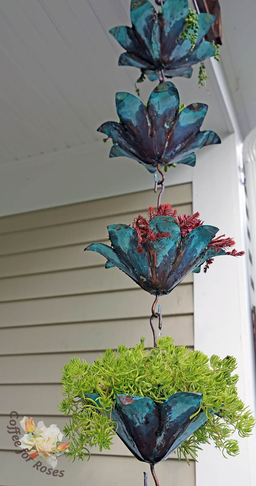 I hung this on one side of my front porch and let the green of the copper determine the color scheme for the pots on the porch this year.