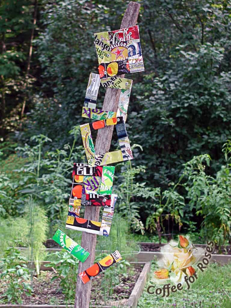 This colorful totem is made from tin-can art on a large limb.