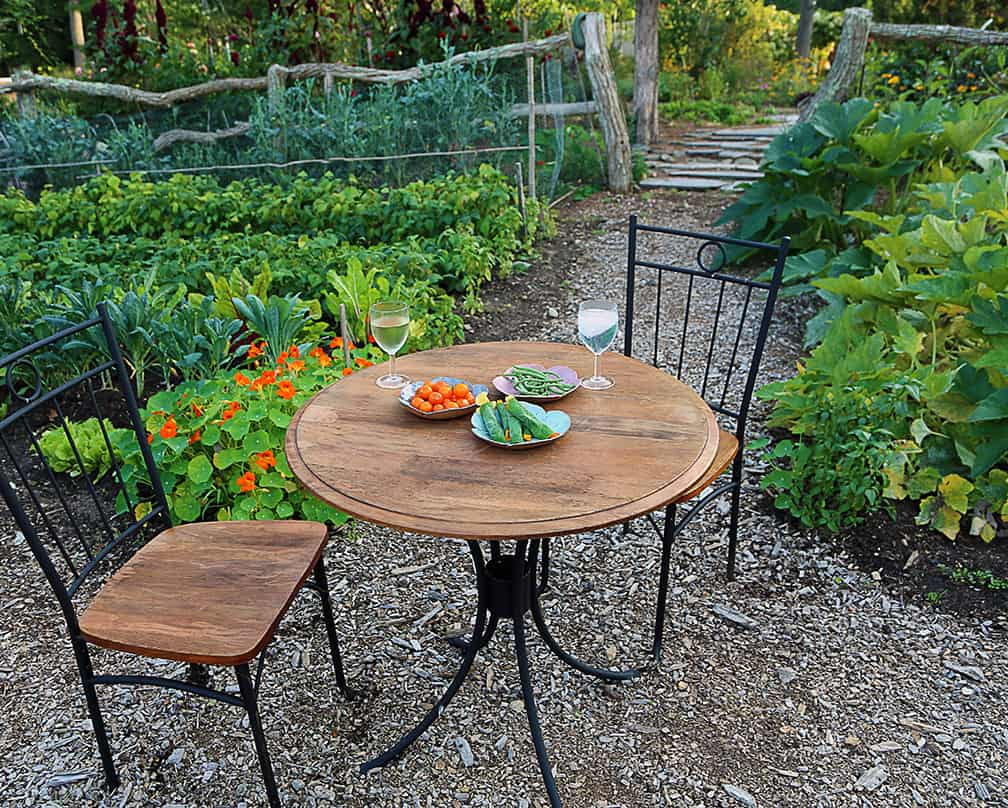 Put a table and chairs in the center of your vegetable garden and toast to how everything is connected to everything else. Cheers!